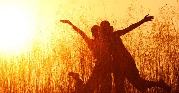 Silhouette of two people happy at a field in the sunset